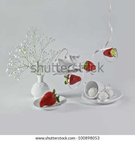 Flying strawberries with white ribbon and decorative dishes. - stock photo