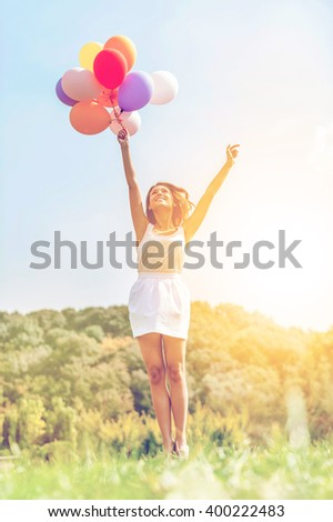 Flying to the sun. Happy young woman holding colorful balloons and flying over a green meadow - stock photo