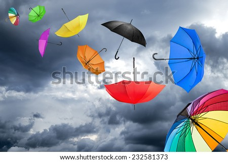 flying umbrellas in front of dark sky - stock photo