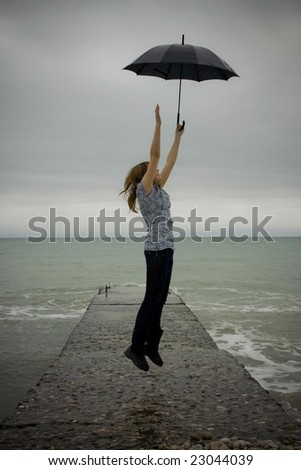 flying up girl with umbrella over sea beach background - stock photo