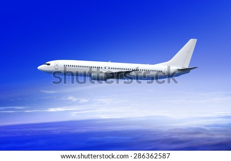 flying white passenger plane in the sky at sunrise - stock photo