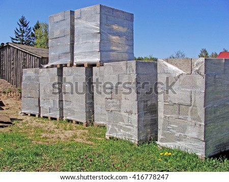 Foam concrete blocks packed in plastic film on wooden pallets for construction.                                - stock photo