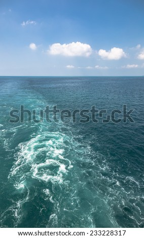 Foamy track of big ship on blue sea   - stock photo