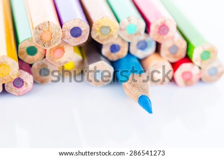 Focus at blue colored pencil with many colored pencil on white background. - stock photo