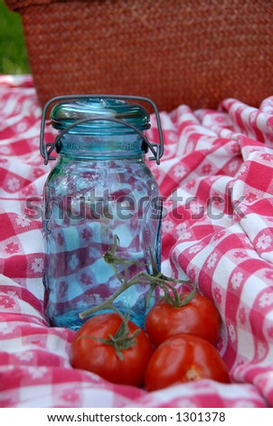 Focus is on the jar.  Blue glass jar with a wire holding the lid and rubber ring  onto it, used for canning fruits and vegetables, sitting on  a vintage table cloth with 3 tomatoes. - stock photo