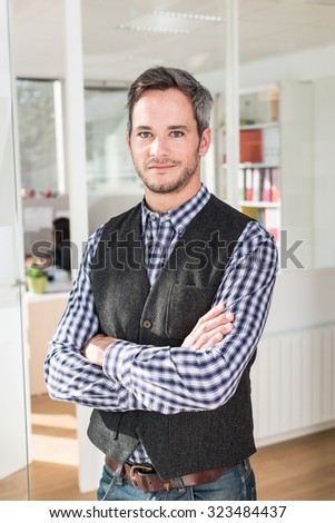 Focus on a smiling Forty years old man with grey hair and beard, wearing a checkered blue shirt. He is standing with his arms crossed in the hallway of a white office, next to a glass door. - stock photo