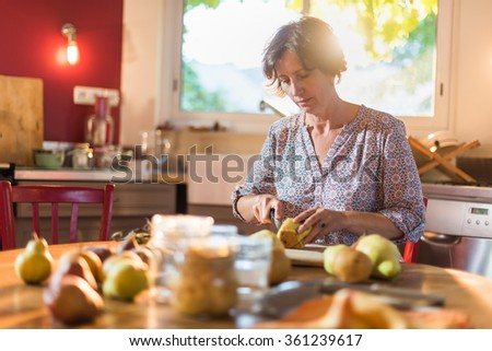 Focus on a woman cutting pears in a luminous kitchen sitting at a wooden table with fruits and utensils around her, to make rustic and old fashioned jar of fruits Blur background. Shot with flare - stock photo