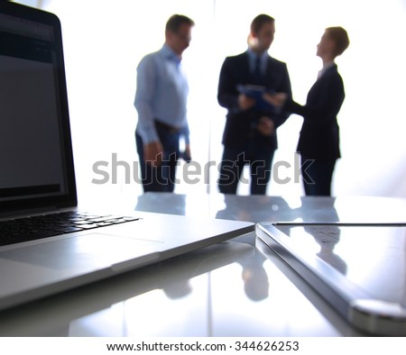 Focus on laptop on the table. Blurred people on background - stock photo