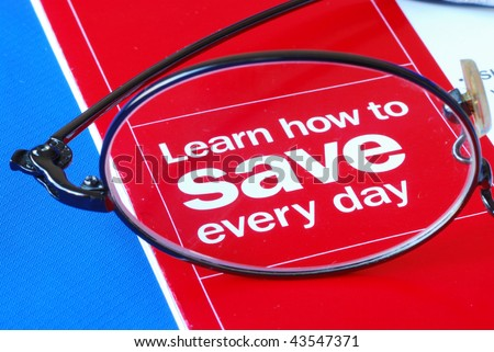 Focus on learning how to save money everyday isolated on blue - stock photo