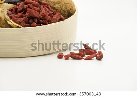 Focus on red goji berry and with some in a bamboo bowl together with other Chinese herbal soup ingredients.  Isolated on white background. - stock photo