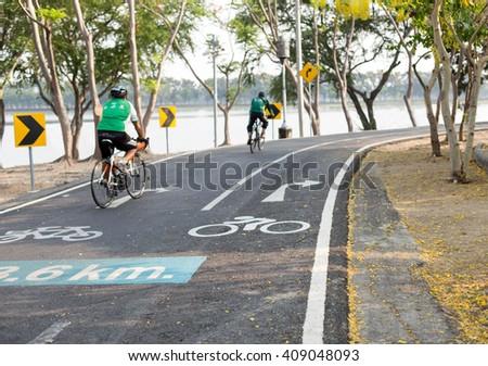 Focus on road sign bicycle lane couple peolple riding bicycle for exersie - stock photo