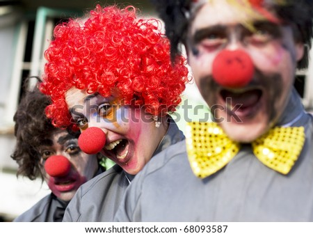 Focus On The Faces Of 3 Crazy Circus Clowns At An Outdoor Birthday Gig Clowning Around In A Funny And Comical Show Of Entertainment - stock photo