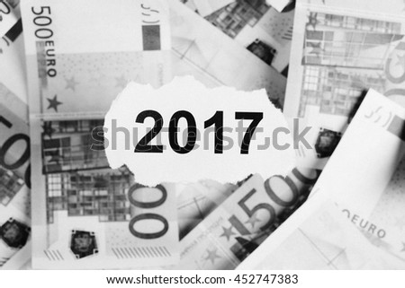 Focus on the words 2017 on piece of torn white paper with USDdollars and EURO currency as a background. Concepts of investment and business. - stock photo