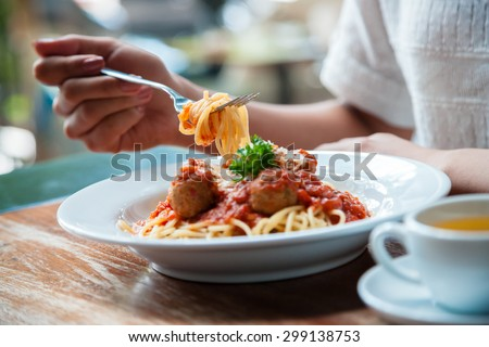 focus on woman eating spaghetti with cup of tea - stock photo