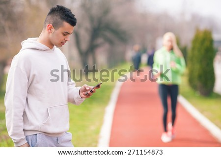 Focus on young coach measuring time for unrecognizable young woman running in the background - stock photo