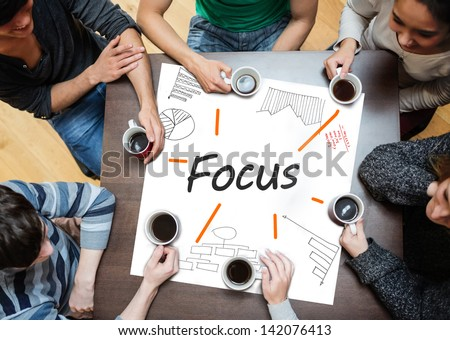 Focus written on a poster with drawings of charts during a brainstorm - stock photo