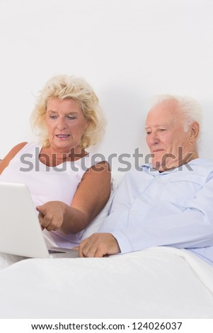Focused aged couple using a laptop on the bed - stock photo