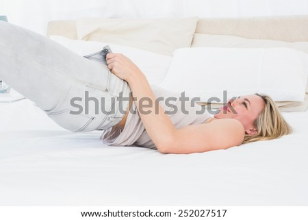 Focused blonde forcing to close her jeans on the bed in hotel room - stock photo
