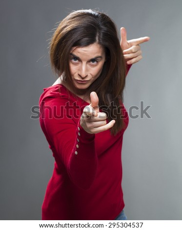 focused brunette woman staring at someone with index finger and torso forward accusing and patronizing someone with fun and self-assurance - stock photo