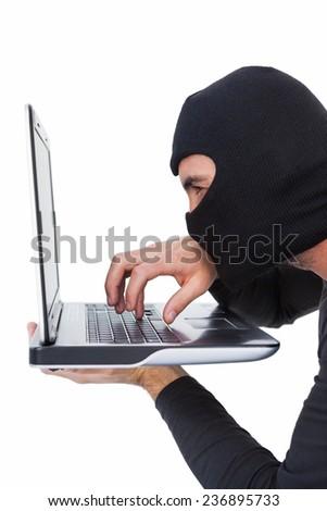 Focused burglar with balaclava typing on laptop on white background - stock photo