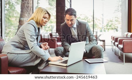 Focused business team having a meeting using laptop in the office - stock photo