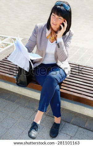 Focused business woman talking by mobile phone and read contract sitting on a park bench, spring mood - stock photo