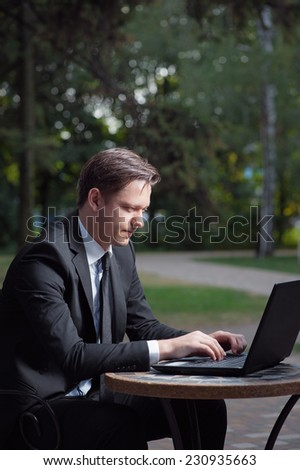Focused businessman. Attractive young man in formalwear working on laptop while sitting at the table outdoors. - stock photo