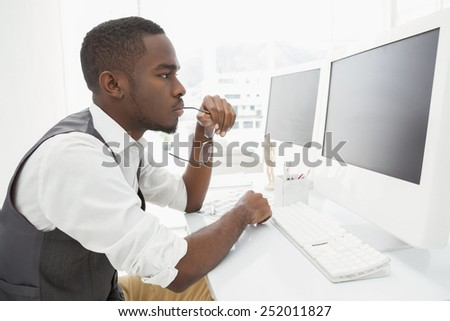Focused businessman holding glasses and using computer in the office - stock photo