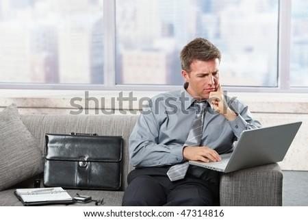 Focused businessman working on laptop computer sitting on sofa in scyscraper building. - stock photo