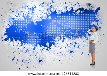 Focused businesswoman against splash on wall revealing blue world map - stock photo