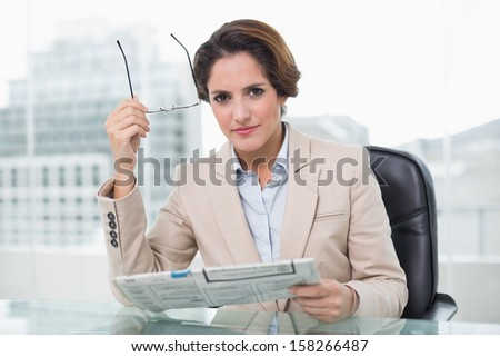 Focused businesswoman holding newspaper in bright office - stock photo