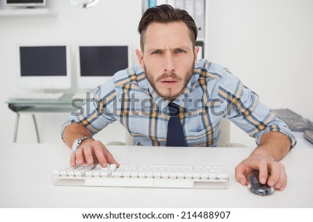 Focused casual businessman working at his desk in his office - stock photo