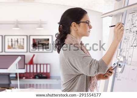 Focused casual caucasian female architect working at drawing board with pen in hand. Wearing glasses, at office. Floor plan, busy, concentration, unsmiling. - stock photo