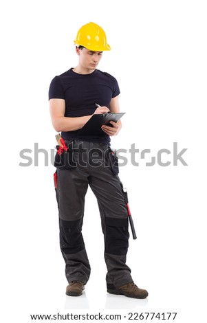 Focused construction worker in yellow helmet holding clipboard and writing.  Full length studio shot isolated on white. - stock photo