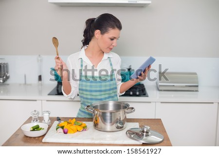 Focused gorgeous woman wearing apron using tablet while cooking in bright kitchen - stock photo