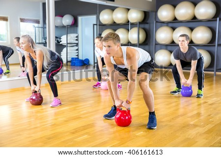 Focused group trains with kettlebells at fitness gym - stock photo