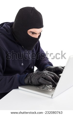 Focused hacker in balaclava hacking laptop on white background - stock photo