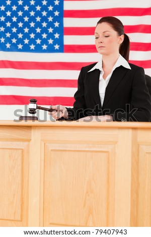 Focused judge knocking a gavel with an American flag in the background - stock photo
