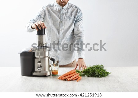 Focused on carrots. Unrecognizable man presses carrots inside metallic professional juicer to make tasty juice for breakfast from fresh carrots, pours in transparent glass. All lying on wooden table. - stock photo