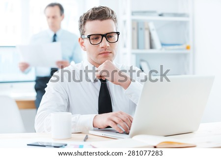 Focused on his work. Thoughtful businessman in formalwear working on laptop and holding hand on chin while sitting at his desk in office - stock photo