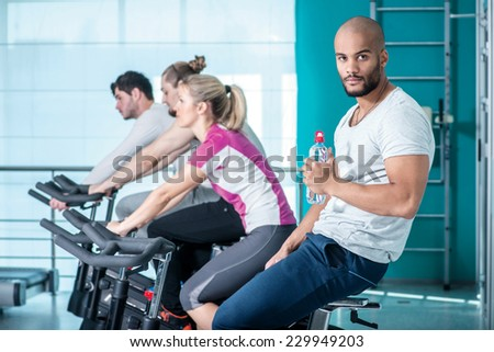 Focused perseverance. Young boy sitting on a stationary bike and holding a bottle of water while his three friends pedal in the gym - stock photo