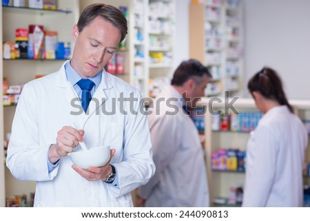 Focused pharmacist using mortar and pestle in the pharmacy - stock photo