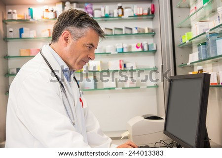Focused pharmacist using the computer at the hospital pharmacy - stock photo