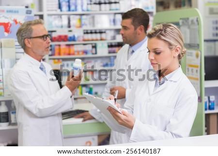 Focused pharmacist writing on clipboard at the hospital pharmacy - stock photo