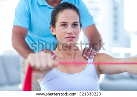 Focused pregnant woman stretching exercise band - stock photo