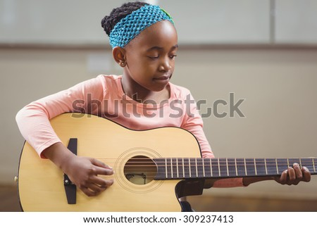 Focused pupil playing guitar in a classroom in school - stock photo