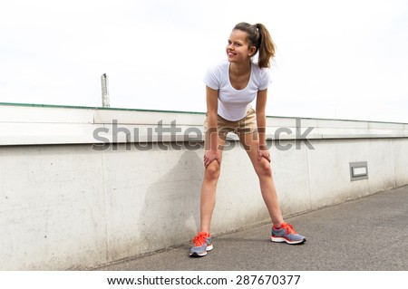 Focused runner outdoors resting with big smile - stock photo