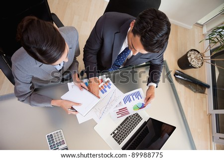 Focused sales persons studying statistics in an office - stock photo