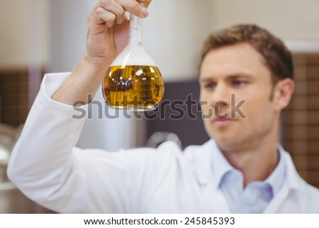 Focused scientist holding beaker with beer in the factory - stock photo