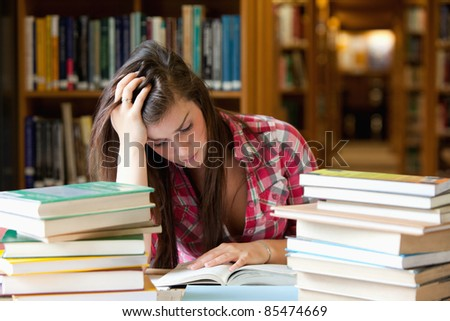 Focused student surrounded by books in a library - stock photo